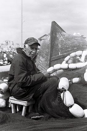 Photo de Azuz, en train de réparer ses filets de pêche à Essaouira, Maroc